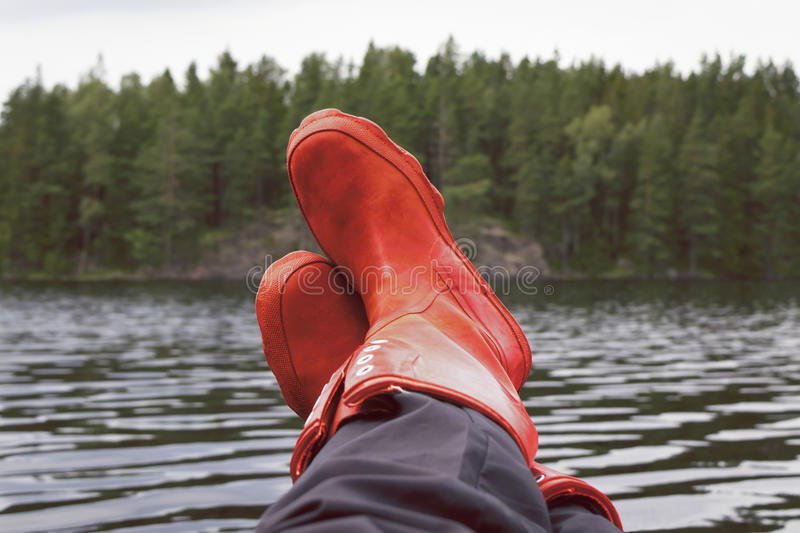 Fisherman taking a break with rubber boots resting on bulwark. Woman fishing by a lake taking a break with red rubber boots resting on the boats bulwark. Forest royalty free stock images