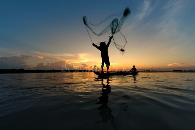 Fisherman throwing net on boat fishing at lake stock photos
