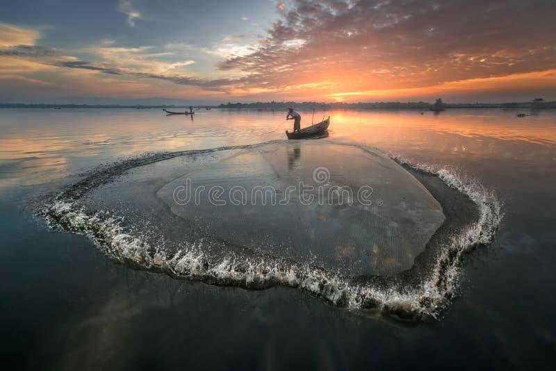 Fisherman Throwing Net Early in the Morning, Taung Tha Man Lake, Mandalay, Myanmar royalty free stock image