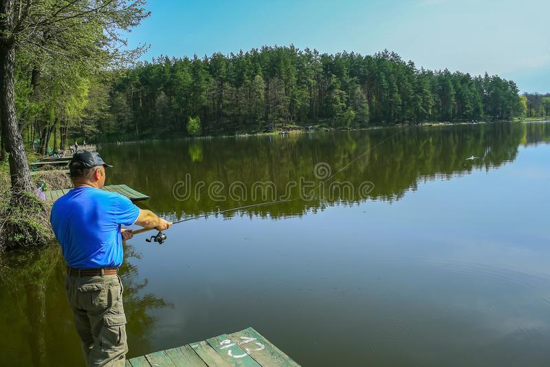 Fisherman throws a fishing pole stock image