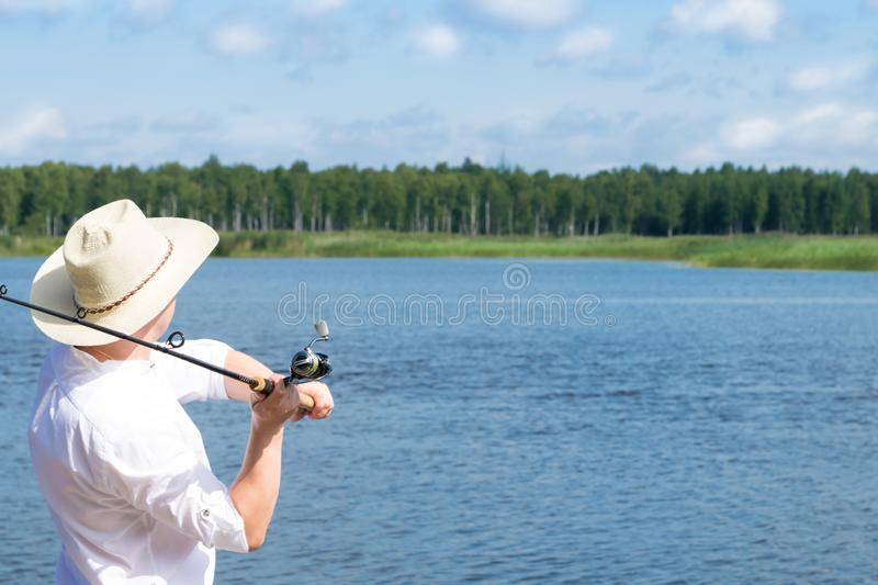 Fisherman throws a fishing rod on the river against the backdrop of a beautiful blue sky royalty free stock photography