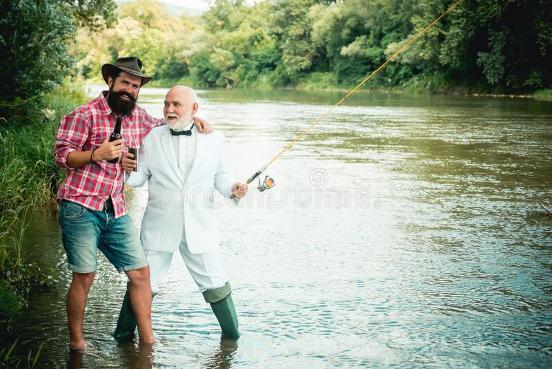 Fisherman and trophy trout. Generations ages: grandfather and father. Still water trout fishing. Happy family concept -. Father and son together stock photography