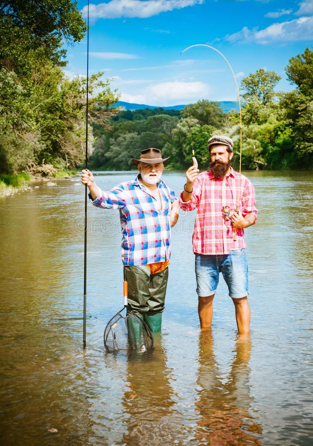 Fisherman and trophy trout. Young man and old mature man fly fishing. Difference between fly fishing and regular fishing royalty free stock photography