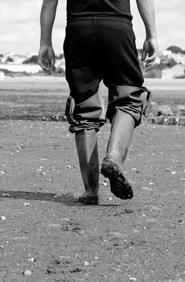 Walking mud boots. Fisherman walking on the mud, with some long boots stock images