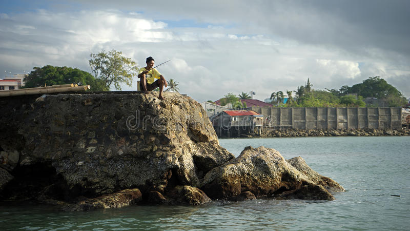 Fisherman on a wharf. A fisherman on a wharf fishing for fish on a bright morning royalty free stock photo