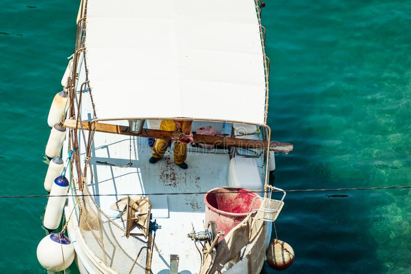 The fisherman working on white fishing boat and fish in the Mediterranean sea port. The fisherman in yellow waders working on white fishing boat  and fish in the royalty free stock images
