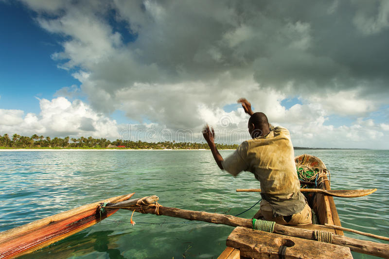 Fisherman in Zanzibar fishing in his boat on a beautiful day royalty free stock photo