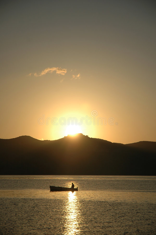 Fishermans boat in the sunrise royalty free stock photo