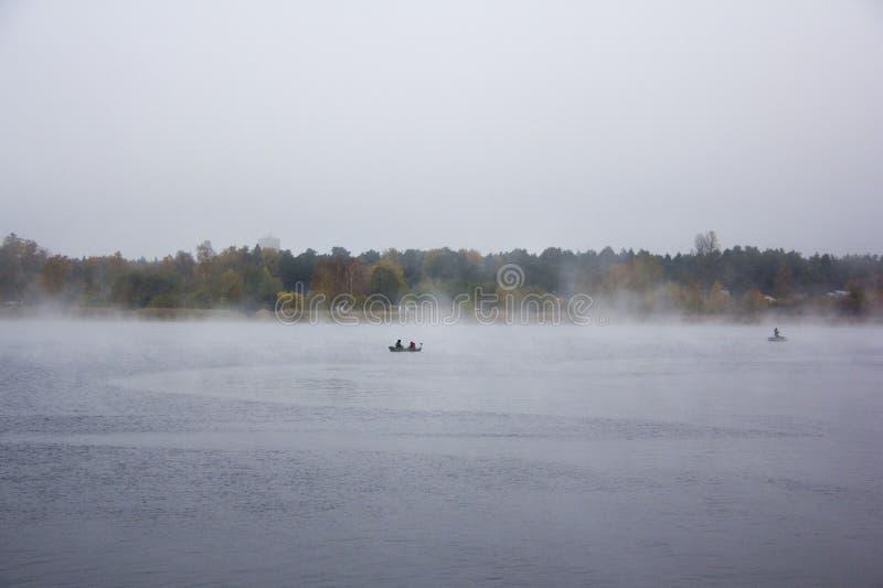 Fishermans in boats fishing in big misty fog stock image