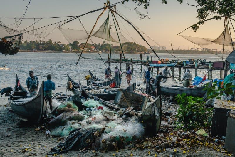 Fishermans die aan de strand Chinese visnetten tijdens de Gouden Uren bij Fort Kochi, Kerala werken royalty-vrije stock foto's