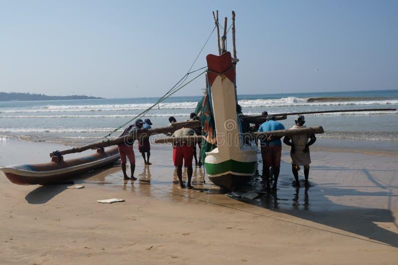 Fishermans roulent de retour leur bateau dans Sri Lanka image stock