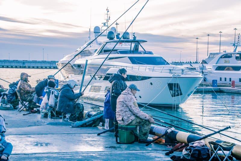 Fishermen on the background of the black sea yachts. Sochi sea port. street fishermen. pier. Central embankment of Sochi. Evening Sochi stock image