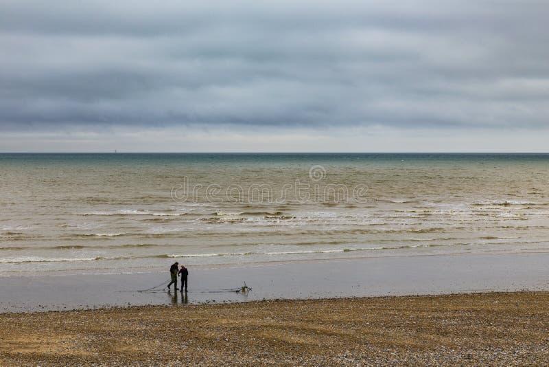 Fishermen on the beach royalty free stock image