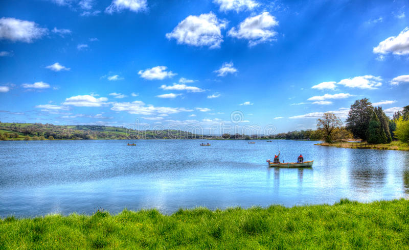 Fishermen in a boat Blagdon Lake Somerset in Chew Valley at the edge of the Mendip Hills south of Bristol like painting in HDR. Fishing Blagdon Lake Somerset in stock photography