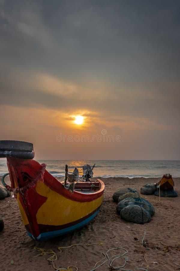 Fishermen boat on shore sunrise view. Fishermen boat on the sea shore with rising sun and fishing nets stock photo