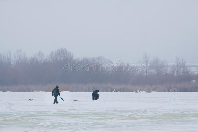Fishermen figures on little, natural, frozen winter lake, covered with snow, fishing rod and ice auger in hands stock images