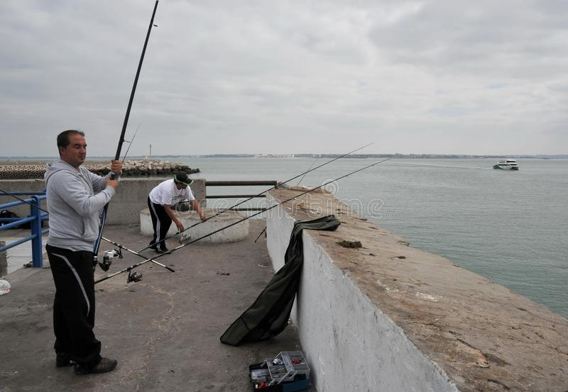 Fishermen are fishing in the harbor of the seaport of Cadiz. royalty free stock photos