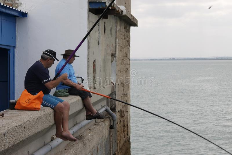 Fishermen are fishing in the harbor of the seaport of Cadiz. royalty free stock images