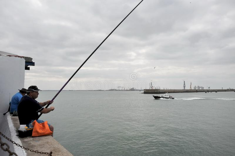 Fishermen are fishing in the harbor of the seaport of Cadiz. royalty free stock photography