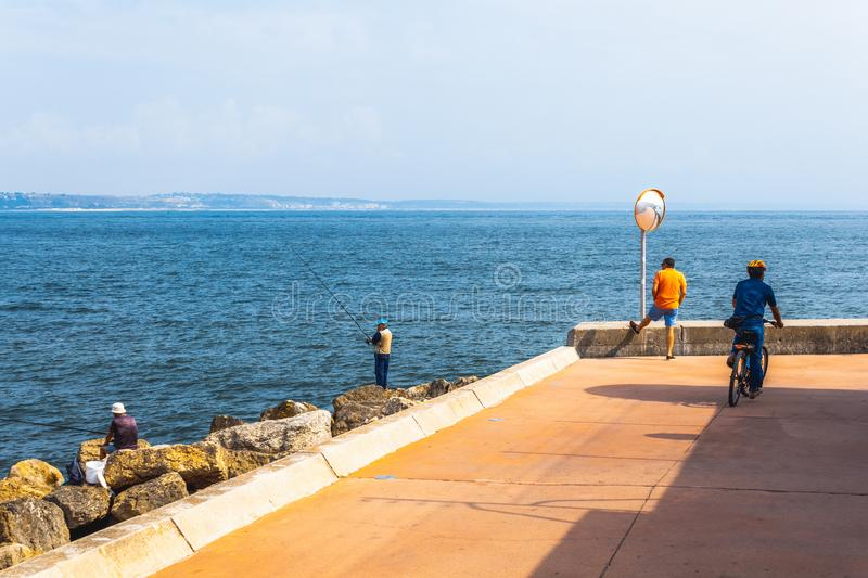Fishermen fishing in Oeiras, Portugal. Deep blue ocean and rocky beach landscape, with shallow waves. Using a fishing rod. Orange shirt, street mirror, bicycle royalty free stock photo