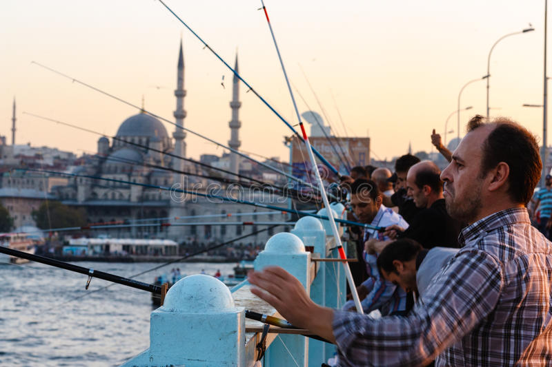 Fishermen on the Galata Bridge. ISTANBUL, TURKEY - SEPTEMBER, 2012: Group of men fish on the Galata Bridge on September 27, 2012 in Istanbul, Turkey stock photography