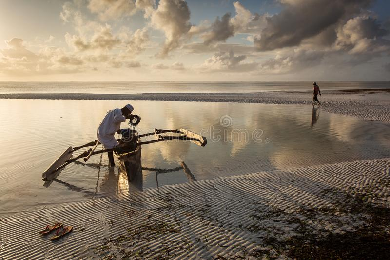 Fishermen going on ocean on traditional fishing boat in Zanzibar stock photos