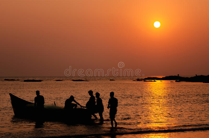 Fishermen going to fishing on a boat in the sea at sunset, Goa, India. Silhouettes of fishermen going to fishing on a boat in the sea at sunset at night and royalty free stock photo