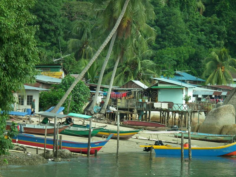 Fishermen houses and fishing boats and pirogues in Pulau Pangkor, Malaysia stock images