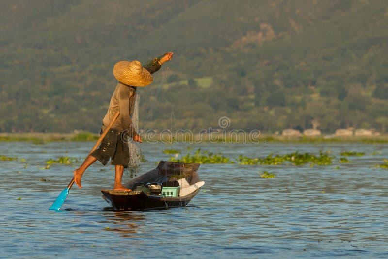 Fishermen at Inle Lake. An unknown fishermen at Myanmar's Inle Lake keeping balance while fishing and leg rowing stock image