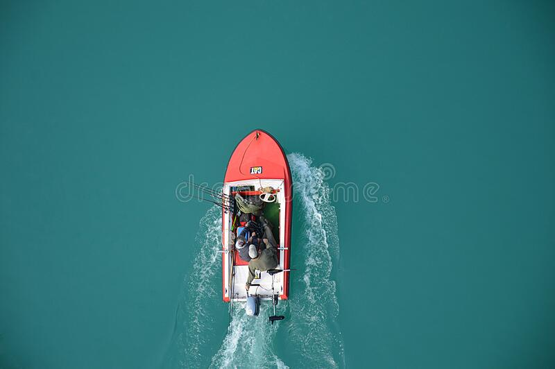 Fishermen on motor boat stock image