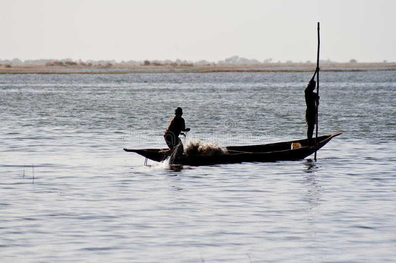 Fishermen in a pirogue in the river Niger (10). Fishermen in a pirogue in the river Niger. The Niger River is an important source of fish, providing food for stock photo