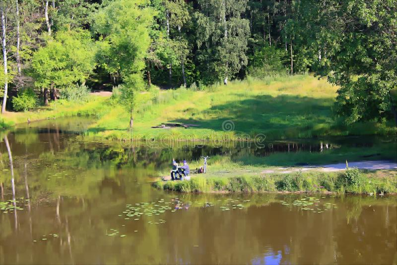 Fishermen on the pond in a forest Park fishing from the shore stock photography