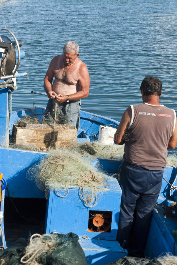 Fishermen repairing fishing nets stock images
