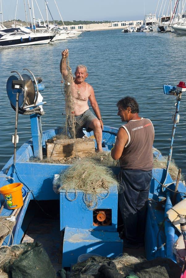 Fishermen repairing fishing nets stock photo