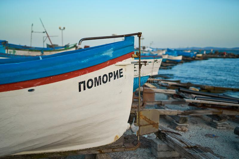 Fishermen`s boats stand on the shore of the seaport of the seaside resort town of Pomorie. POMORIE, BULGARIA - JUNE 30, 2019: Fishermen`s boats stand on the royalty free stock photo