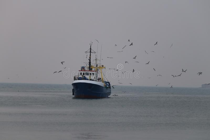 Fishermen and seagulls, blue sea stock images