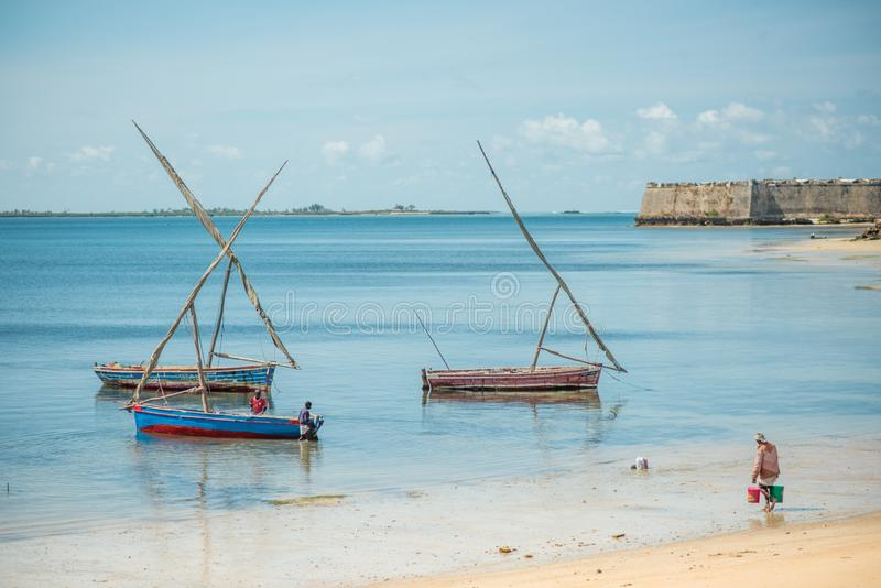 Fishermen and small fishing boats moored at Ilha de Mocambique beach, with Fort royalty free stock image