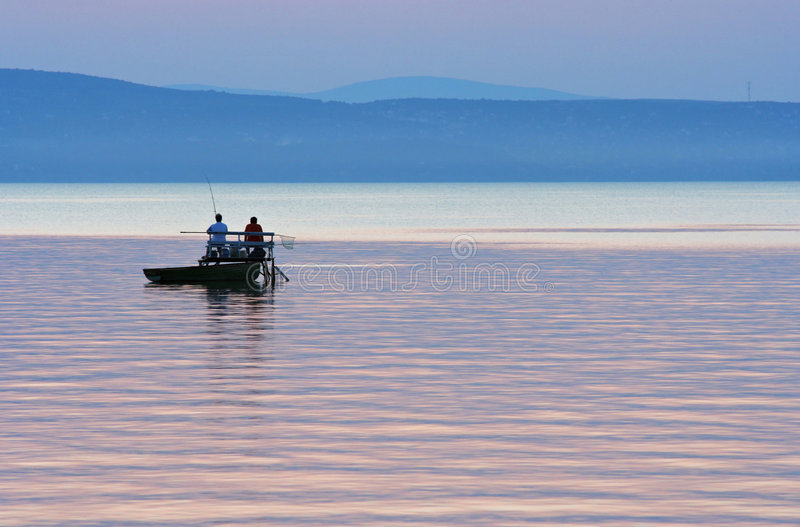 Fishermen after sunset stock photo