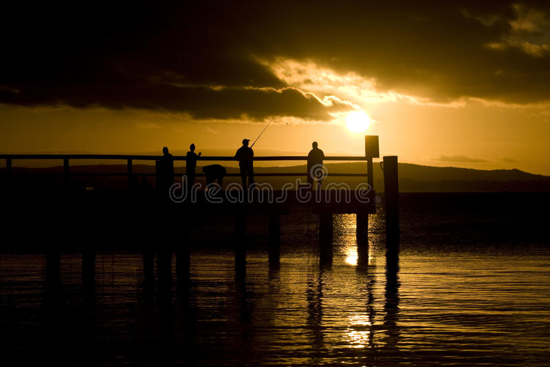 Fishermen at sunset royalty free stock photography