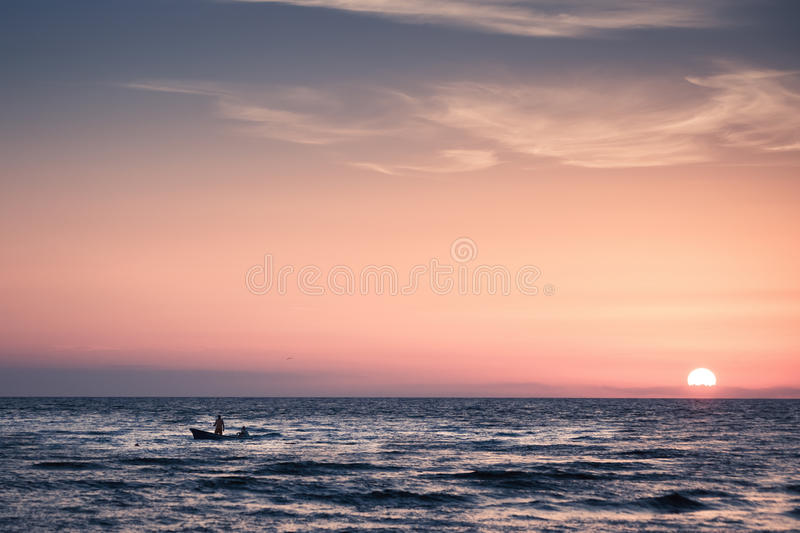 Fishermen at sunset. Small boat with fishermen at sea at sunset royalty free stock image