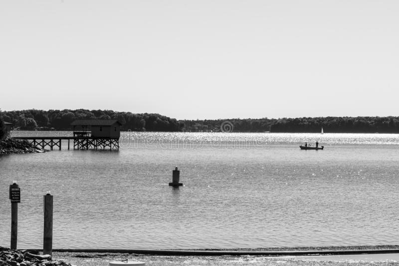 The Fishermen Tradition. Taken at Ramsey Creek Park off of Lake Norman. Black and white. Fishermen in the distance next to an old pier. Cornelius, North Carolina stock image
