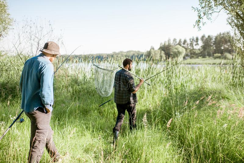 Fishermen walking on the green lawn. Two fishermen walking with fishing rod and net on the green lawn near the lake in the morning royalty free stock images