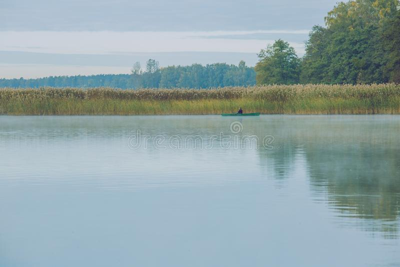 Fishermens with boats, nature and lake. Fog and big trees. stock photography