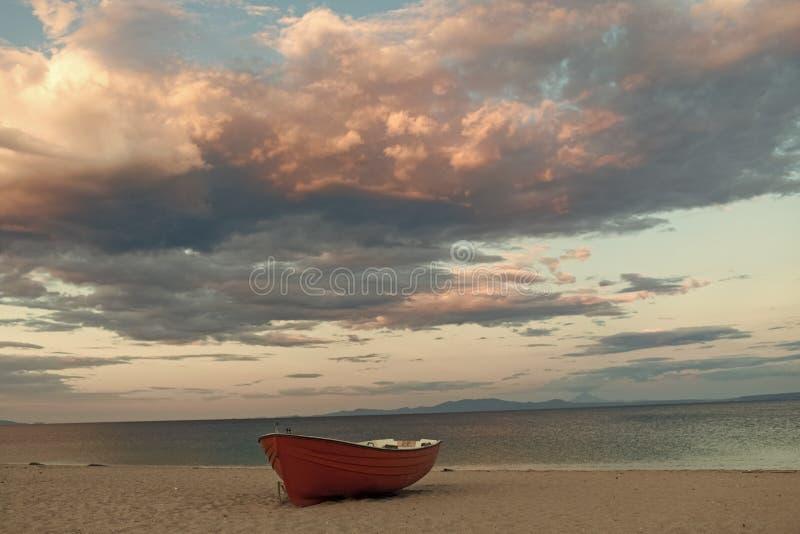Fishermens fartyg på seacoasten, på sand på solnedgången med horisonthavet på bakgrund Fiskebåt på stranden i afton Resor royaltyfri fotografi