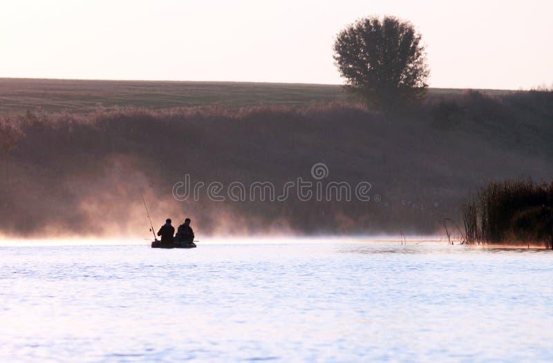 Fishermens in peschereccio ad alba di estate in tempo nebbioso fotografie stock