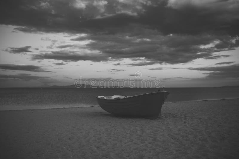 Fishermensboot bij zeekust, op zand bij zonsondergang met horisontoverzees op achtergrond Reis en rust concept Achtergrond van stock afbeelding