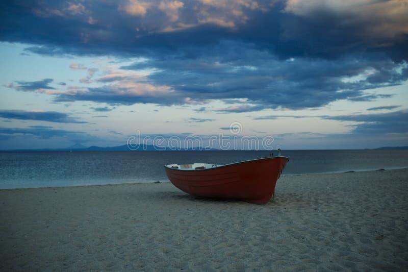 Fishermensboot bij zeekust, op zand bij zonsondergang met horisontoverzees op achtergrond Reis en rust concept Achtergrond van stock afbeeldingen