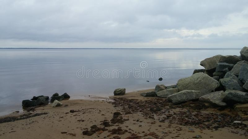 Fishers Landing. Landscape photography of the river shore with rocks sky and clouds royalty free stock images