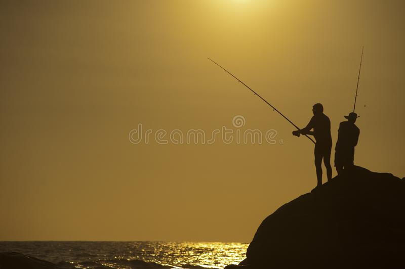 Fishers on a rock beside the sea royalty free stock photos