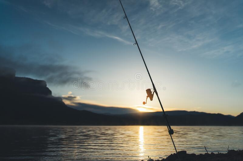 Fishery concept, outline fishing rod at sunrise sunlight, hobby sport on mist evening lake, catch fish on river on background. Night sky foggy mount, holiday royalty free stock photography